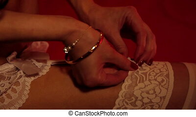 A female hands takes of her stockings - A woman takes off...