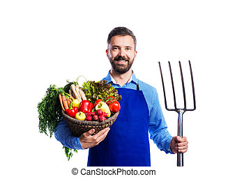Young handsome gardener in blue apron. Studio shot on white...