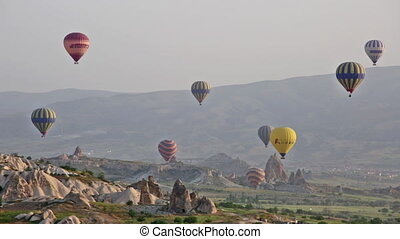 Multi-colored balloons fly over rocks Cappadocia
