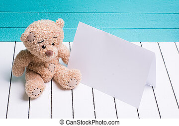 bear sitting on white wooden floor in blue-green background with blank note