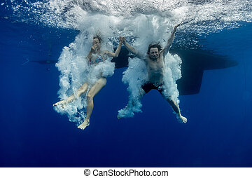 Jump underwater - Underwater view of the young couple having...