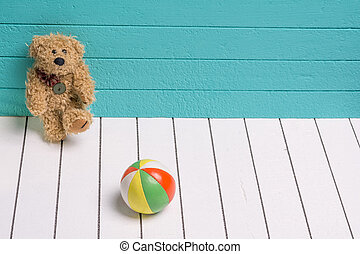 Teddy bear on a white wooden floor in blue-green background playing with ball