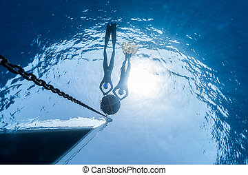 Freediving - Two free divers relaxing on the buoy linked to...