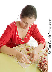 Woman making meat dumplings from stuffing and dough