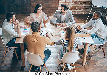 Discussing new possibilities. Top view of young business people discussing something while sitting at the office desk together