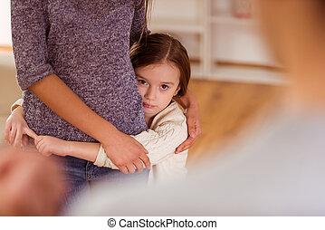 Quarrels between parents - ?hild hugs her mother and...
