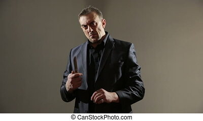 male gangster in a business suit with a knife. hold the...