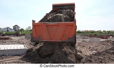 Dump truck is unloading soil.