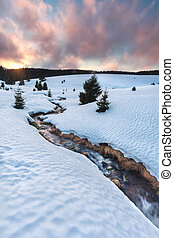 mountain river on snow meadows at sunset near Todtnauberg,...