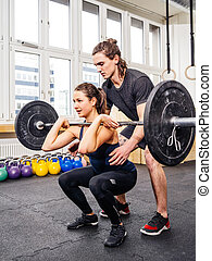 Woman doing squats at crossfit gym - Photo of a young woman...