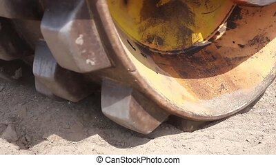 Huge road roller with spikes is com - Construction worker is...
