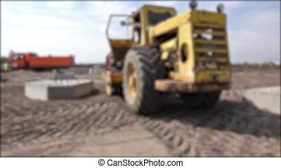 Blurred view on a huge road roller - Construction worker is...