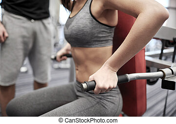 close up of woman flexing muscles on gym machine - sport,...