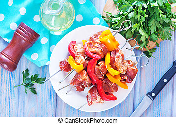 meat and vegetables - raw meat kebab with vegetables on a...