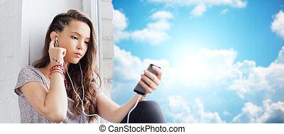 teenage girl with smartphone and earphones - people,...