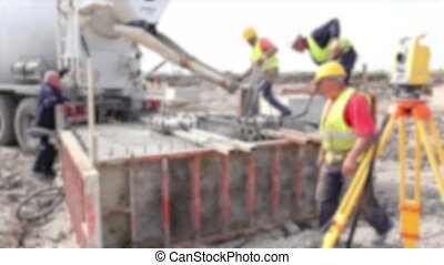 Blurred view at pouring concrete in - Workers at building...