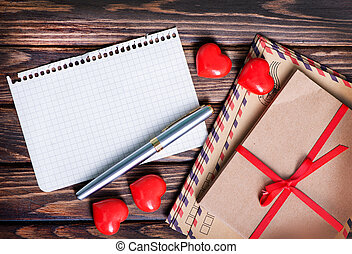 envelopes and red hearts on the wooden table