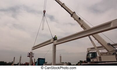 Height worker is placing truss - Concrete truss is hanging...