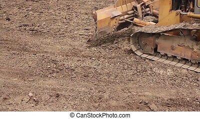 Bulldozer machine is leveling earth