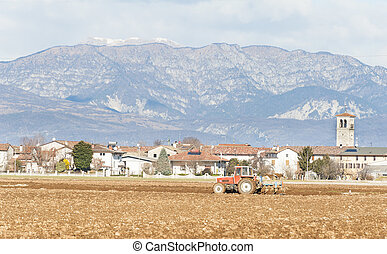 Agricultural landscape with tractor plowing.