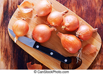raw onion on wooden board and on a table