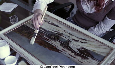 Designer apply varnish on painting - A woman sits at a table...