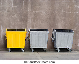 garbage can - one yellow and two zinc garbage tanks near the...