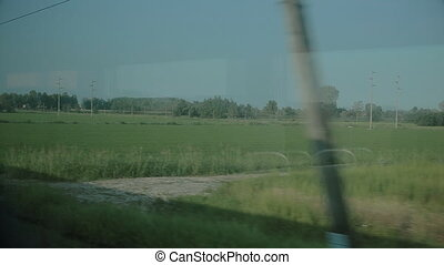 View from the window of a moving train - View on a green...