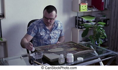 Man wipes the dust painting - A man sitting at the table and...