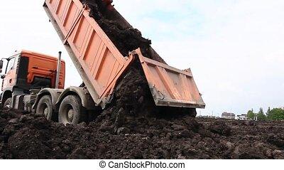 Many dump trucks are unloading soil