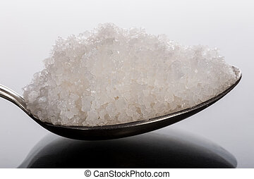 Sea coarse salt in spoon close-up Side view