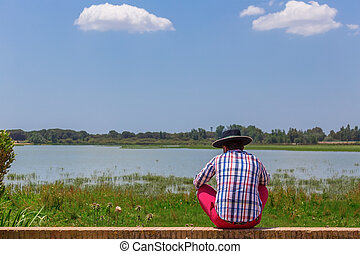 The Spaniard sits on the shore of the lake reflects. The...