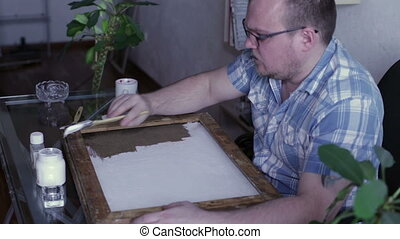 Man covers the canvas ground - A man is sitting at a table...