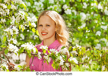 Cute teenager girl with white flowers on pear tree - Cute...