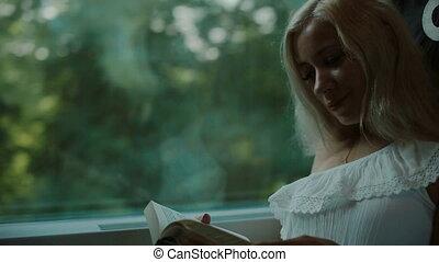 Beautiful blonde reading a book in the train - Beautiful...