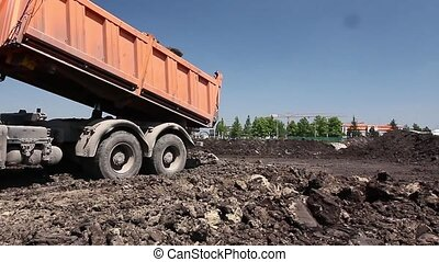 Dump truck is unloading soil - Heavy wheels are working at...