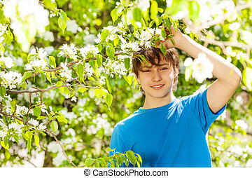 Happy teenager boy holds branch with white flowers on pear...