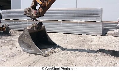 Excavator changes his bucket. - Excavator is replacing tool...