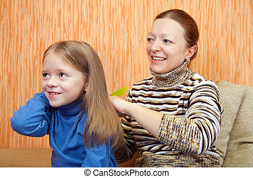 mother combs the hairs of daughter at home