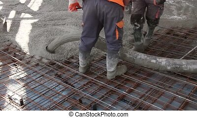 Workers are spreading concrete - Construction workers are...