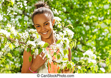 African teenager girl with white pear flowers - Portrait of...