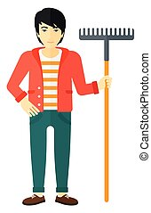 Man standing with rake. - An asian man standing with a rake...