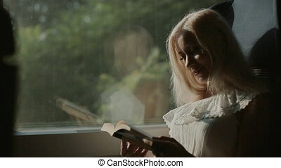 Inquisitive blonde reading a book sitting in the car of the...