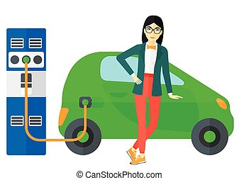 Charging of electric car - An asian woman charging her...