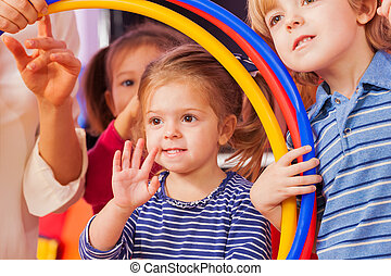 Little girl wave hand looking though hoop - Close portrait...