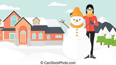 Woman posing near snowman - An asian woman standing near a...