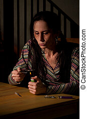 Woman cooking heroin in a spoon - Woman cooking heroin in a...