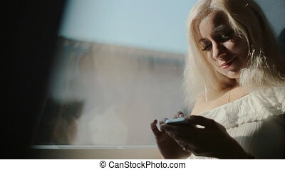 Attractive blonde writing sms on mobile phone