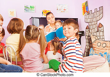 Kids sit around teacher and listening to story - Group of...
