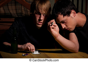 Two young men with heroin or cocaine on table